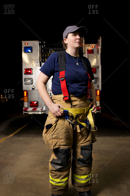 A firewoman stands in front of a fire truck
