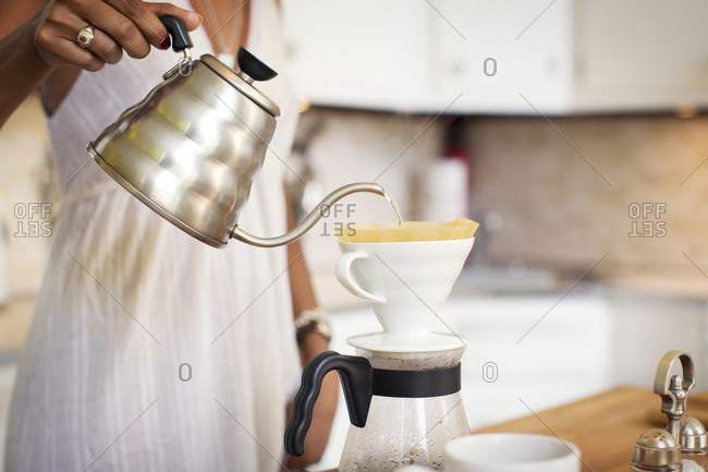 A woman pours boiling water into a pour over coffee maker