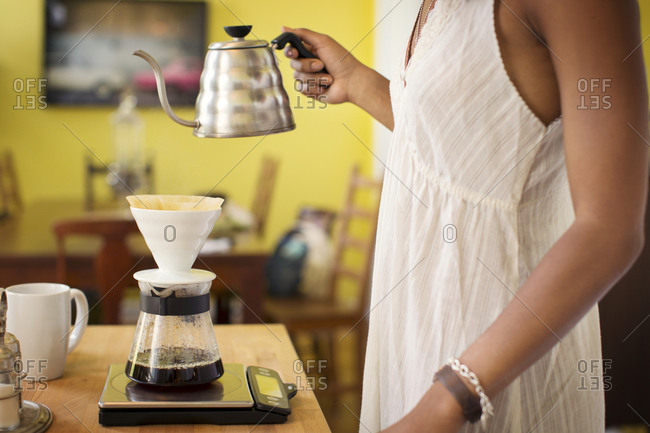 A woman makes coffee using a pour over coffee maker