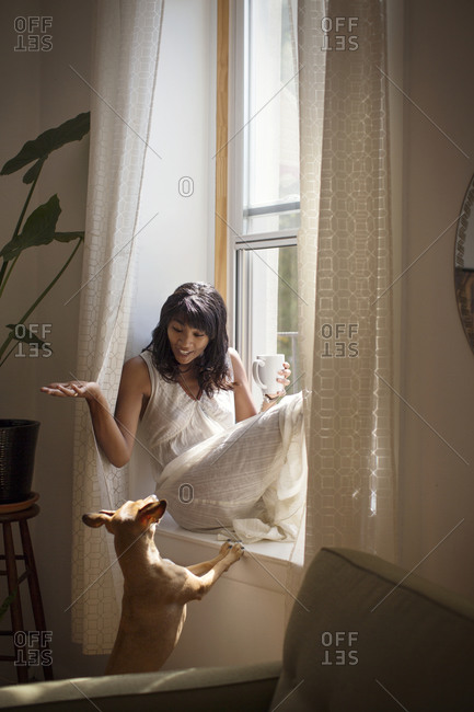 A woman talks with her dog while sitting on her windowsill