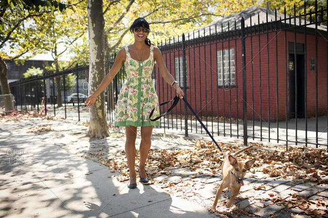 A woman walks her dog on a city sidewalk