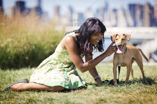A woman pets her dog in a park