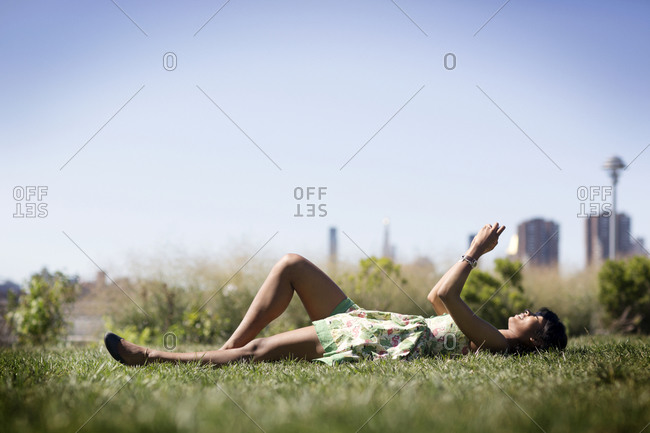 A woman lays on her back in a park and looks at a smartphone