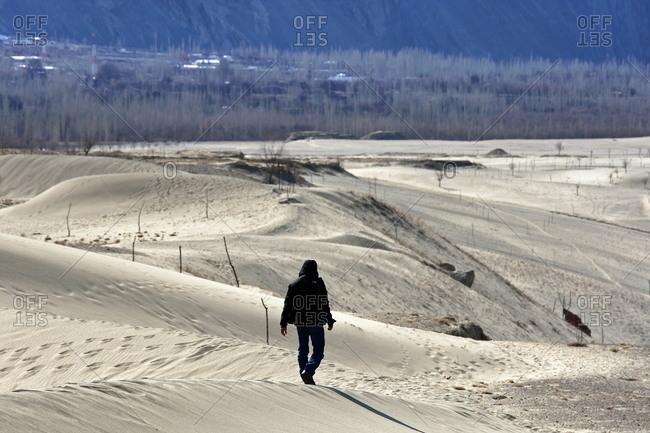 A man walks through the desert at the base of a mountain