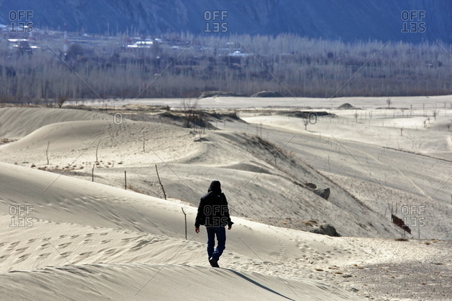 A man walks through the desert at the base of a mountain