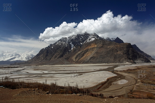 A dried riverbed at the foot of a mountain