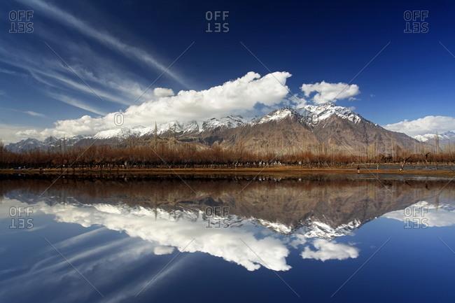 A clear lake reflecting Pakistani mountains