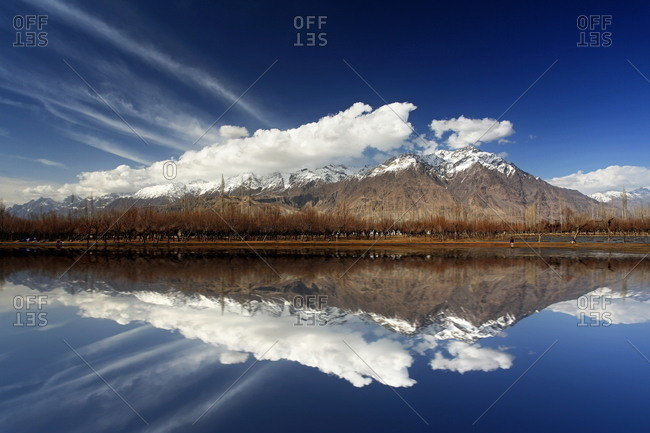 A clear lake reflecting Pakistani mountains