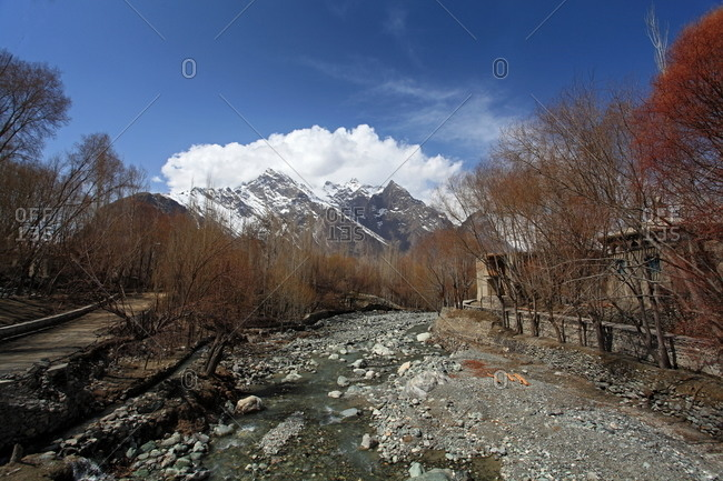 A river running through a small Pakistani town in the foothills of a mountain range