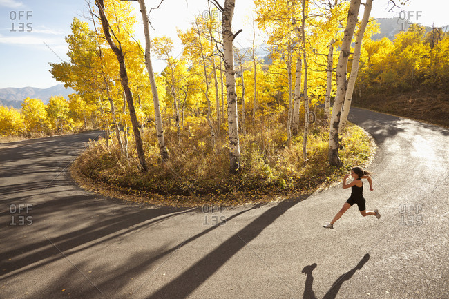 Young woman running along a road
