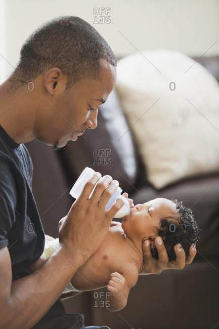 Father feeding newborn baby