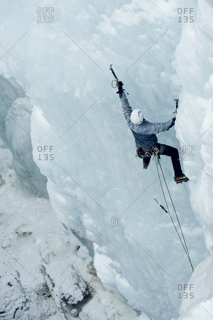 Man climbing up a wall of ice
