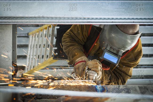 Construction worker grinding metal