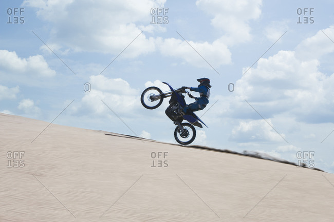 Man riding a motorcycle on a sand dune