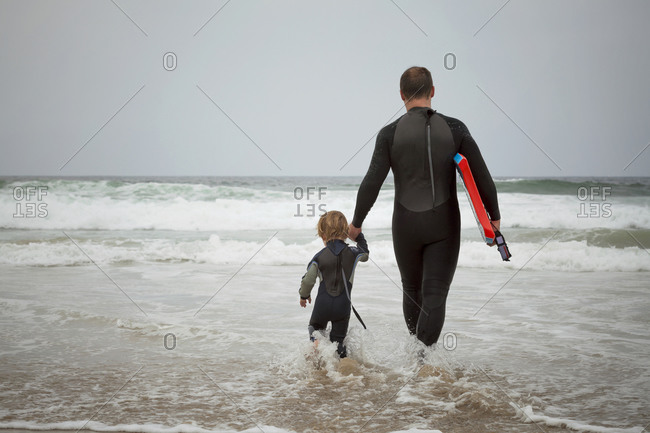 Father and son wading into the ocean