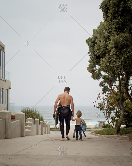 Father and son in wetsuits walking towards the ocean