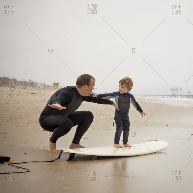 Father teaching his son to surf