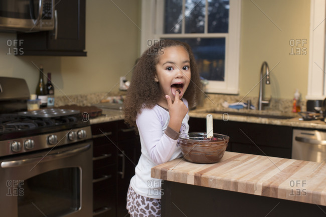 Little girl licking cookie batter off her finger
