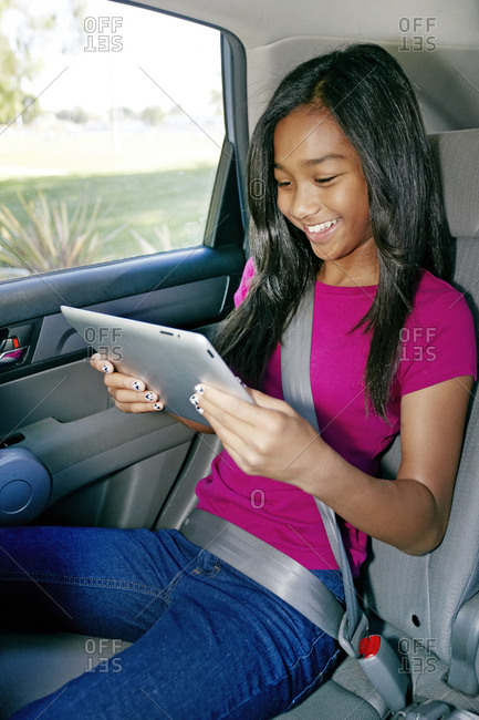 Girl using a digital tablet in the car