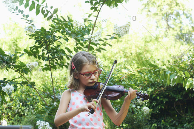 Little girl playing violin outdoors