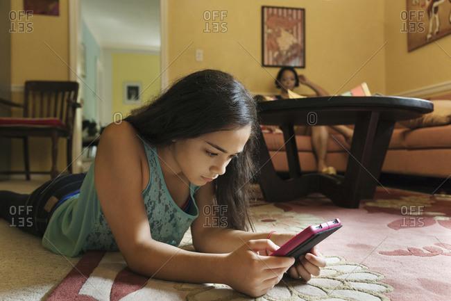 Girl reading a digital tablet on the floor