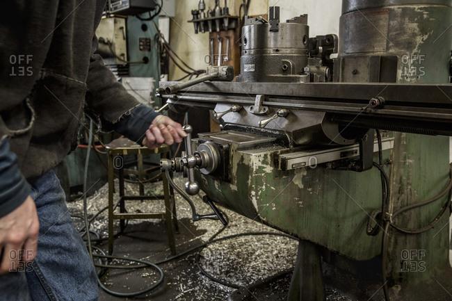 Worker using machinery in metal shop