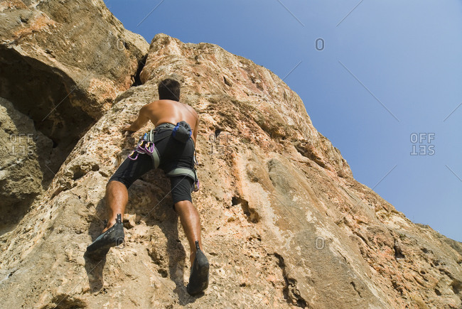 Low angle view of man climbing up a rock wall