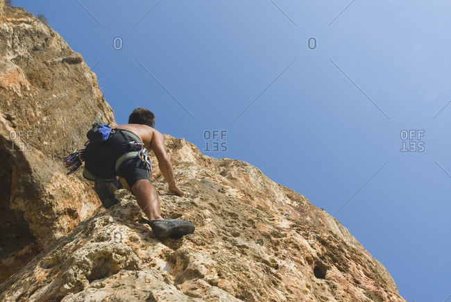 Low angle view of man scaling rock face