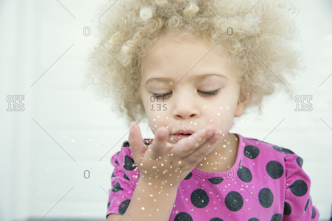 Girl blowing glitter from hand