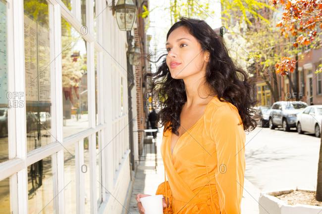 Woman window shopping on city sidewalk