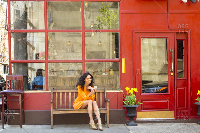 Woman using cell phone outside a cafe