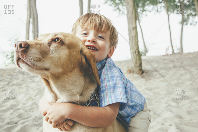 Boy hugging dog on beach