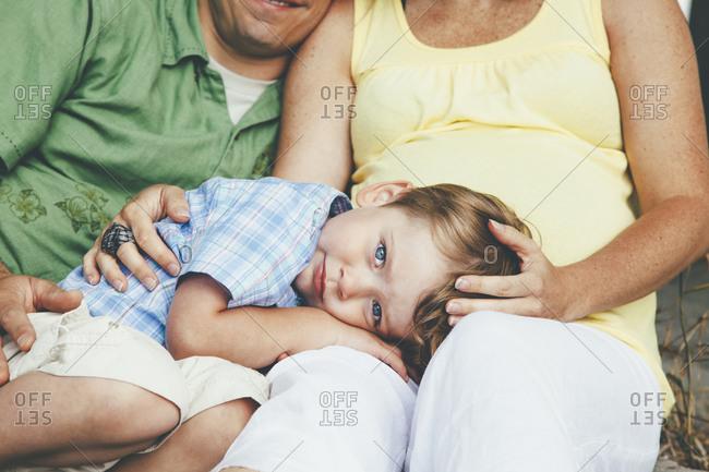 Boy resting in his parent's lap