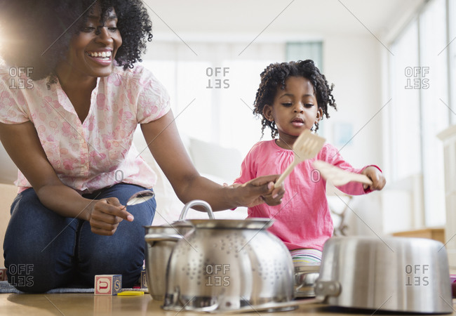 Mother and daughter playing with dishes