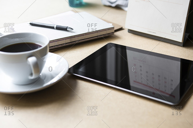 Tablet computer on a table with a notebook and coffee