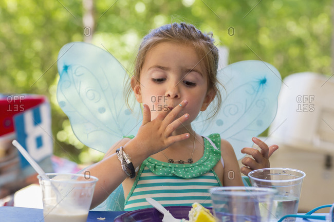 Young girl eating cake in a butterfly costume