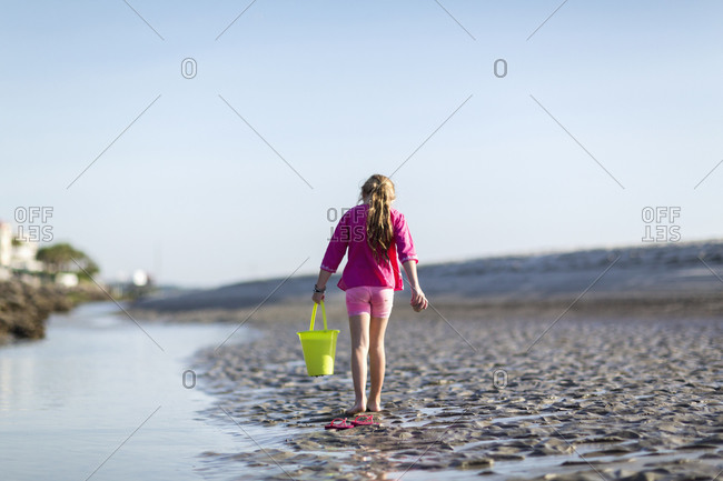 Young girl carrying a bucket on a beach