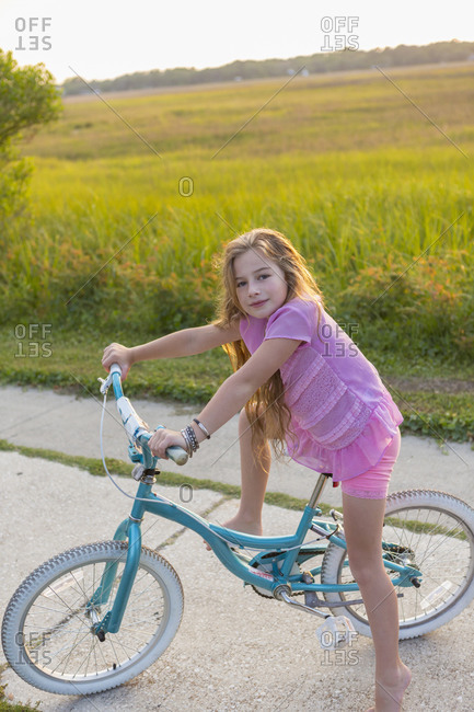 Blonde girl riding a bicycle at a field