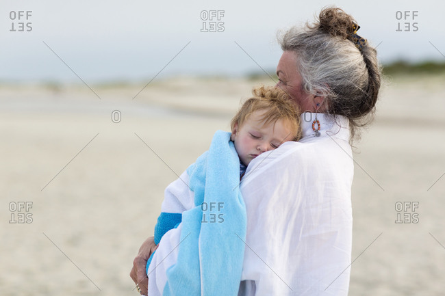 Senior woman carrying her grandson on a beach