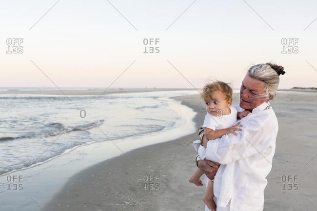 Senior woman carrying her grandson on a sandy beach