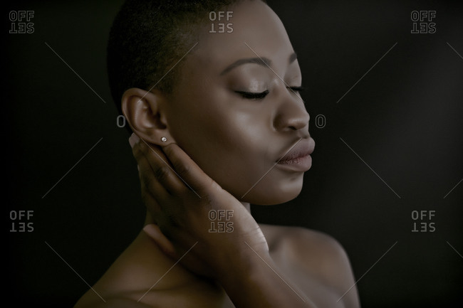 Young woman touching her neck
