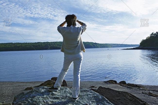 Woman standing at a lake shore