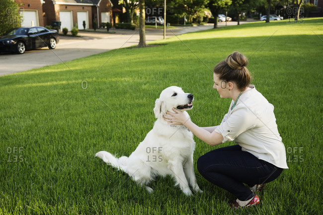 Woman petting dog in a park