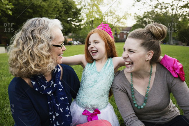 Women bonding with a redhead girl in a park