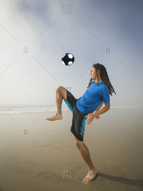 Teenage boy doing kick-ups with a soccer ball