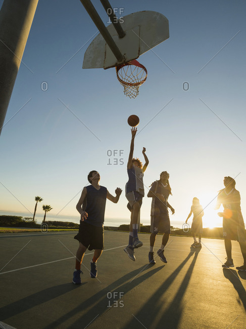 Basketball team playing on a court at sunset
