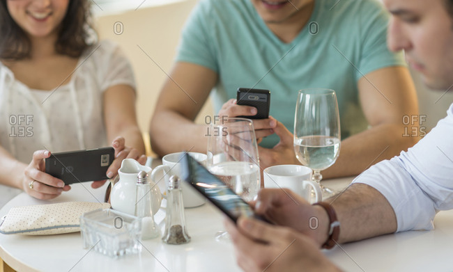 Friends using cell phones in a cafe