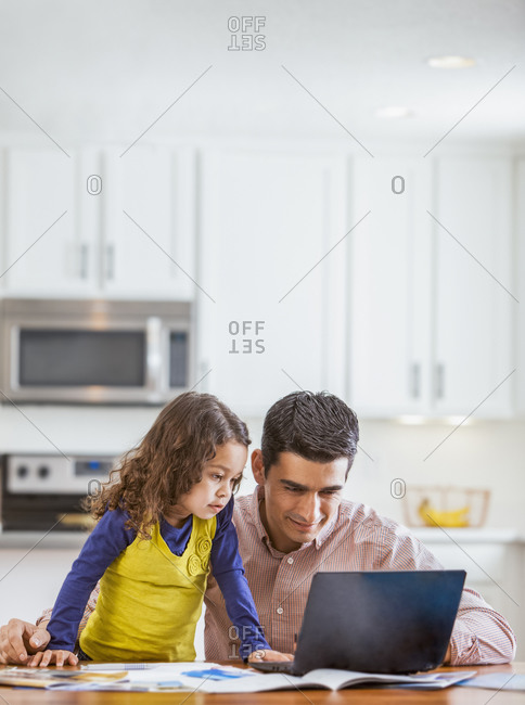 Father and daughter using laptop in a kitchen