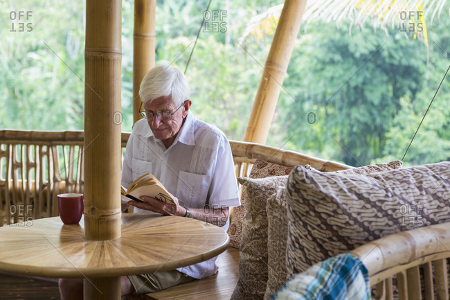 Man reading a novel at a bamboo table