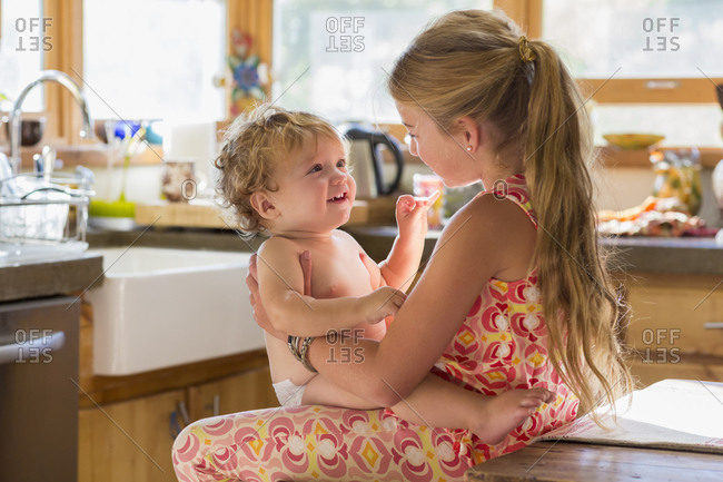 Young girl holding her little brother in a kitchen